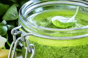 Pesto sauce in a glass jar, cheese,