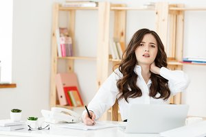 Businesswoman suffering neck pain