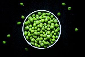 Fresh peeled green peas in white bow