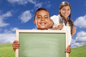 Hispanic Boy and Girl In Field Holdi