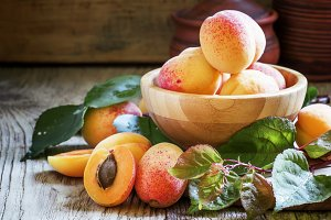 Fresh apricots with leaves in a bowl