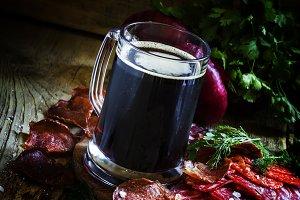 Big glass of dark foam beer, sausage
