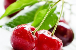 Red sweet cherry, white wooden backg
