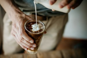 Man pouring milk in iced coffee