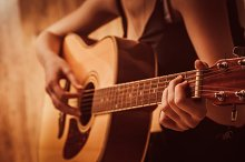 woman's hands playing  acoustic guit