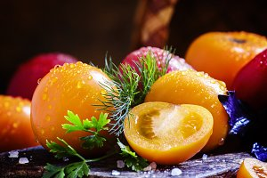 Whole and cut orange tomatoes, dill,