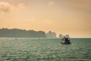 Thai boat floating between cliffs