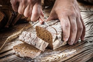 Man's hands cutting bread on the woo