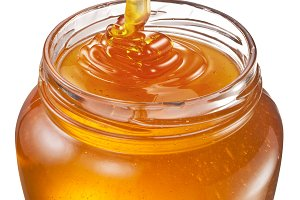 Honey flowing into glass jar. File c