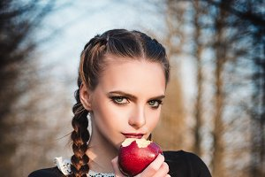 Cute young girl eating apple