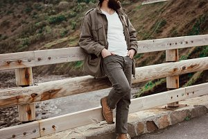 Hipster man leaning against a wooden