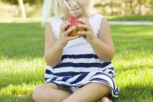 Little Girl Sitting and Eating Apple