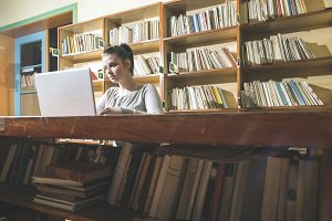 Student girl and laptop in a library