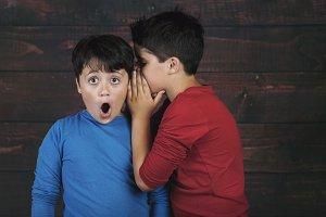 two boys whispering secret