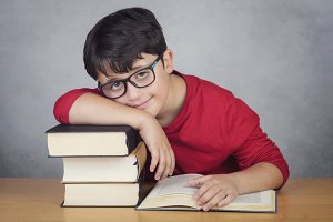 smiling little boy leaning on books