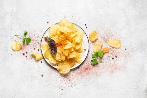 Dish with potato chips on a gray bac