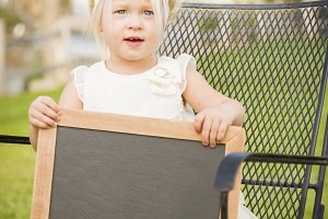 Cute Baby Girl in Chair Holding Blan
