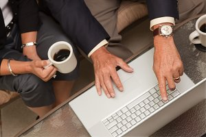 Man and Woman Using Laptop with Coff