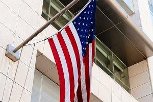 American flag waving against modern