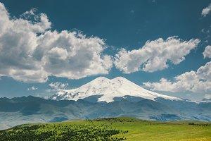Elbrus Mount And Green Hills At Sunn