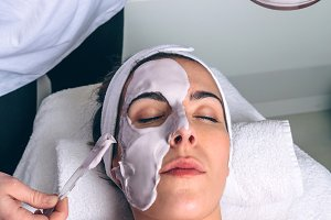 Beautician applying facial mask to w