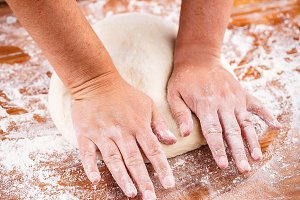 Woman's hands knead dough