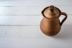 Clay jug on wooden table background.