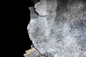 Damaged concrete grey wall on a blac
