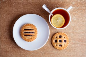 Cup of tea and lemon, cookies with