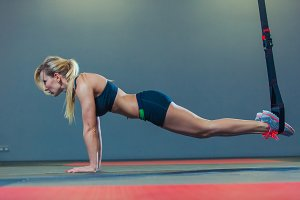 Sporty woman doing TRX exercises in