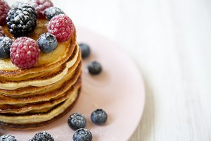 Pancakes with berries on a pink