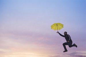 man jumping with yellow umbrella