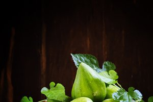 Cut green figs and a wooden bowl of