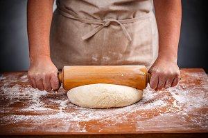 Housewife flattening a dough