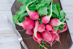 bunch of radishes with leaves on a w