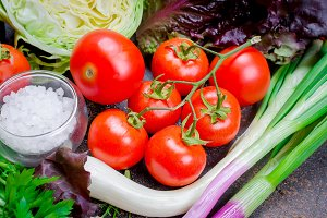 Raw vegetables for salad on dark bac