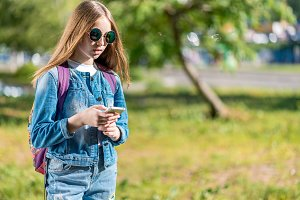 Girl schoolgirl behind backpack
