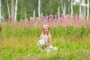 Little blonde girl picking up flower