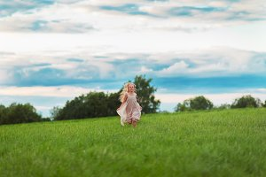 Little blonde girl running on a gree
