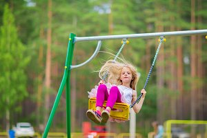 Little blonde girl smiling swinging