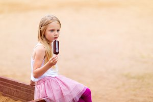 Little girl eats stick ice cream bar