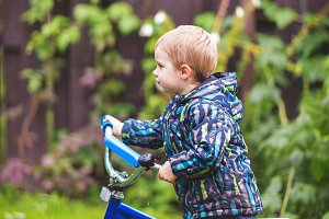 Little boy riding bicycle outdoors