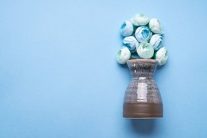 Vase with decorative flowers on blue