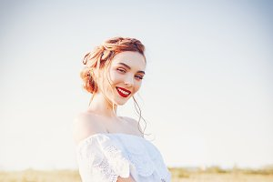 Cute smiling young woman in field