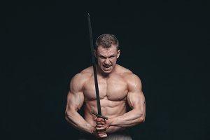 Bodybuilder man posing with a sword