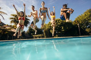 Friends jumping into a swimming pool