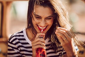Beautiful young woman drinking soda