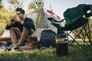Man in tent drinking coffee
