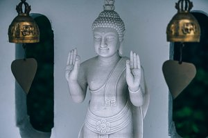 White Buddha Posing Between Two Bell