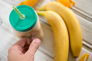 Glass jar with banana and orange smo